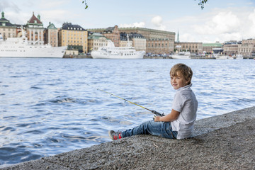 Portrait of boy fishing in river, old town in background