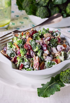 Broccoli Salad with Bacon, Dried Cranberries and Sunflower Seeds in white Salad Bowl.