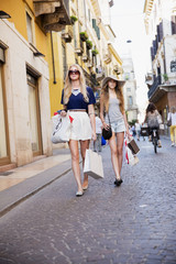 Mother and daughter with shopping bags walking in street