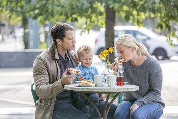 Parents with son eating cake in sidewalk cafe