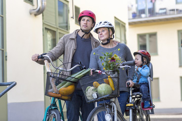 Mid adult couple and child with bicycles