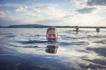 Father and children swimming in lake
