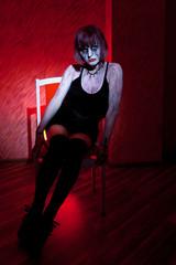 vampire girl posing sitting on a red