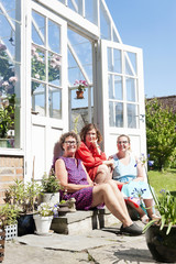 Three women sitting in front of greenhouse