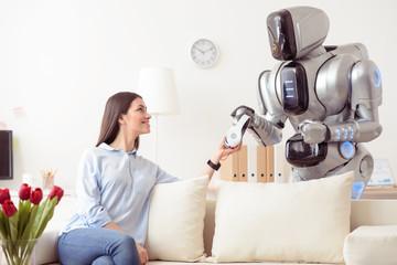 Positive girl giving headphones to modern robot