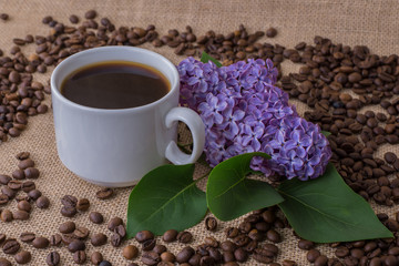 Coffee cup with lilac  on burlap background with beans