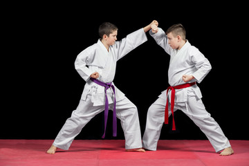 Two boys in white kimono fighting isolated on black background