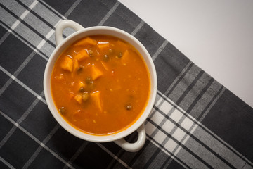 Sweet potato, carrot and green lentil soup with coconut milk and canned tomatoes on the gray tablecloth