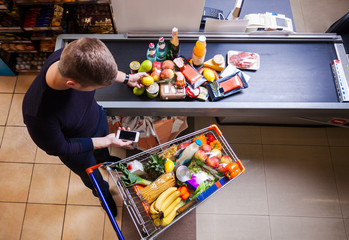 Young man putting goods on counter in supermarket