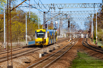 Yellow blue train on the track moving through in Poland.
