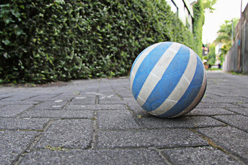 The blue and white soccer ball on the cobblestone road was forgotten by children, Kuta, Bali, Indonesia