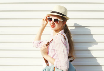 Fashion pretty woman in sunglasses and hat over white background