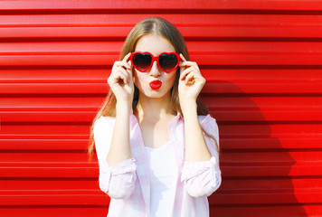 Pretty woman in red sunglasses blowing lips kiss over colorful b