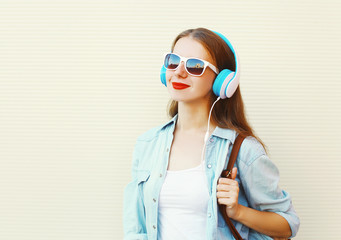 Young woman listens to music in headphones over white background