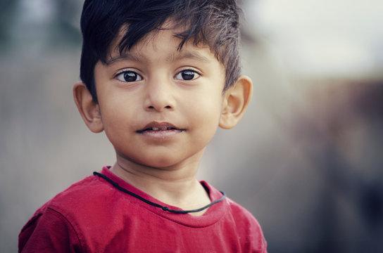 Sick poor boy child portrait looking sideways with soar lips