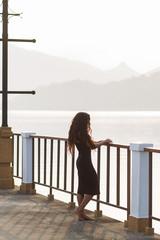 Woman in black dress watching sunrise at the empty bridge. Morni