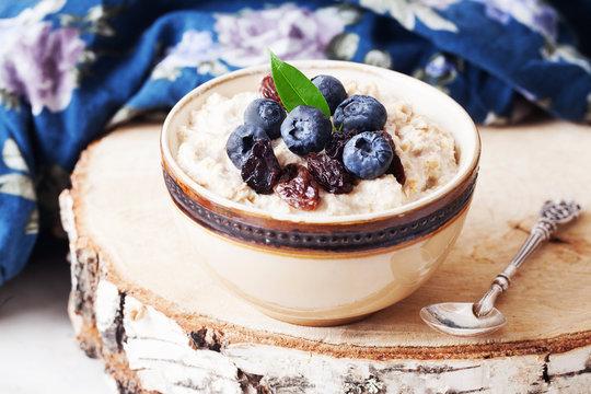 Oatmeal porridge with berries still life, blueberries, raisins, birch, cut down
