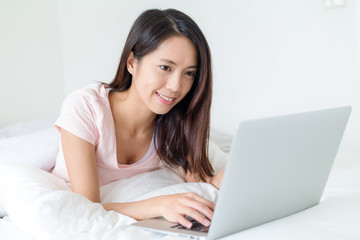 Woman lying down the bed in front of her laptop