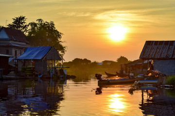 Boats and floating village houses on a river at sunset