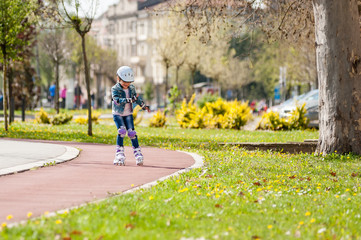 Little caucasian girl on inline skates with full protective equipment