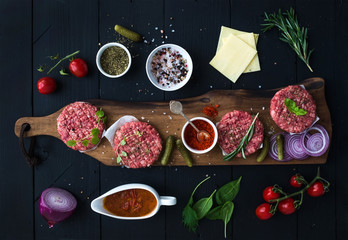 Ingredients for cooking burgers. Raw ground beef meat cutlets on wooden chopping board, red onion, cherry tomatoes, greens, pickles, tomato sauce, cheese, herbs and spices over black background, top