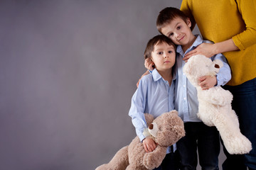 Sad little children, boys, hugging their mother at home, isolate