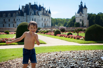 Cute little boy, playing in the rain in front of a castle in Fra