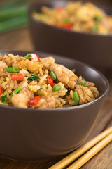 Homemade Chinese fried rice with vegetables, chicken and fried eggs served in brown bowl with chopsticks on the side (Selective Focus, Focus on the top of the dish)