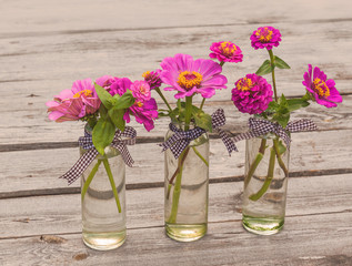 Three zinnias bouquet on a wooden table