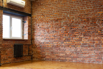 Room with a window, red brick walls and wooden flooring of boar