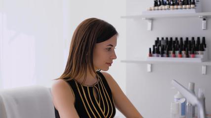 Beautiful brunette doing a manicure in a bright room
