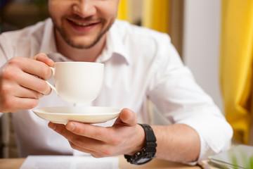 Handsome guy is enjoying hot drink