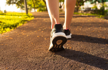 Closeup of woman's feet walking in the park. Wall mural