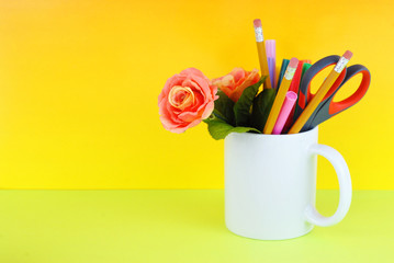 White coffee mug filled with markers, pencils, scissors and a silk rose on a green and yellow background good for secretary's day, or administrative professionals day
