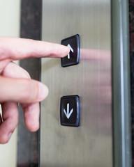 Hand pressing elevator button.