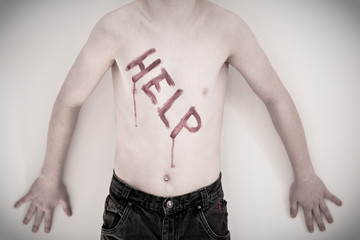 Shirtless boy with help written on chest