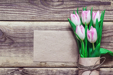 Blank card and bouquet of pink tulips in a brown paper on grunge