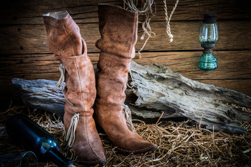 Still life with traditional leather boots on barn background