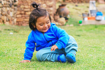 Little latin girl sat on the grass