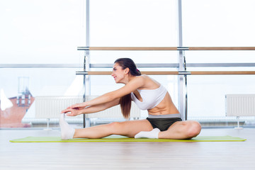 fitness, sport, training and people concept -  Happy young woman stretching before running in gym