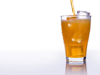 Pooring soft drink in a glass with ice