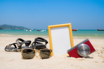 Summer time concept,frame,camera,shoes and glasses on the beach