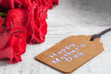 Happy Mother's Day text with wet red roses on white rustic wooden table