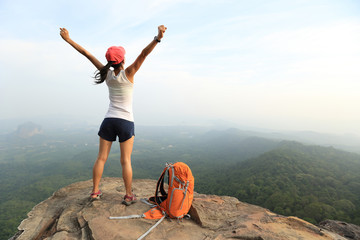 cheering young asian woman hiker open arms on seaside mountain peak