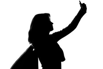 silhouette of a woman with shopping bags doing selfie