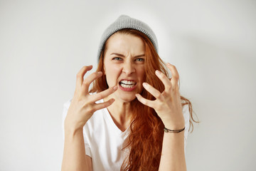 Close up isolated portrait of young annoyed angry woman holding hands in furious gesture. Young female with red hair in white T-shirt and cap. Negative human emotions, face expressions. Film effect
