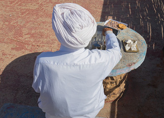 Old man in traditional Morocco's closes drink tea with sweets.