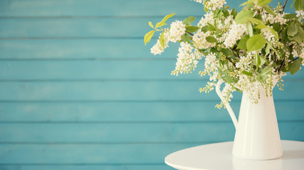 Beautiful white flowers in a vase, on blue wooden background