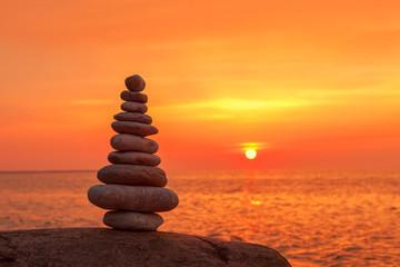 Concept of harmony and balance. Rock Zen on sunset background.