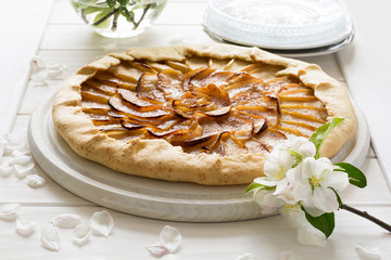Open pie or galette with apples decorated apple blossom on white wooden desk